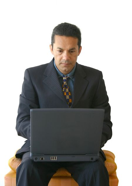 business man working on a laptop sitting on a stool