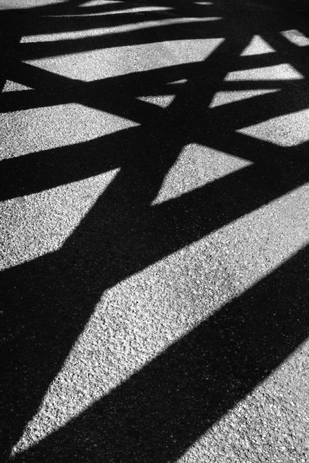 Abstract of structural shadows: Crisscross of long shadows on public park land beneath a timber approach span of a railroad bridge built in 1898 across the Illinois River, in black and white