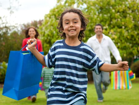 Family running through a park with shopping bags