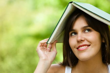Thoughtful female student with a notebook on top of her head