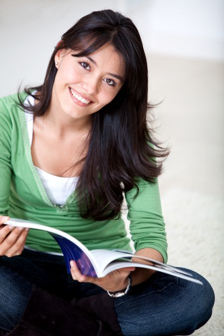 Beautiful woman sitting on the floor studying