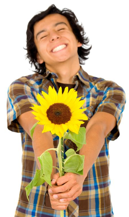 Casual happy man with a big smile handing out a sunflower – isolated over a white background with focus on the flower