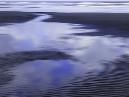 Serene abstract of tide pool draining through channel across sandy beach back toward the ocean along Pacific coast of Olympic Peninsula in Washington, for themes of nature, transience, the environment