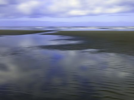 Serene morning abstract of large tide pool reflecting partly cloudy sky on sandy beach along Pacific coast of Olympic Peninsula in Washington, for themes of nature, transience, the environment