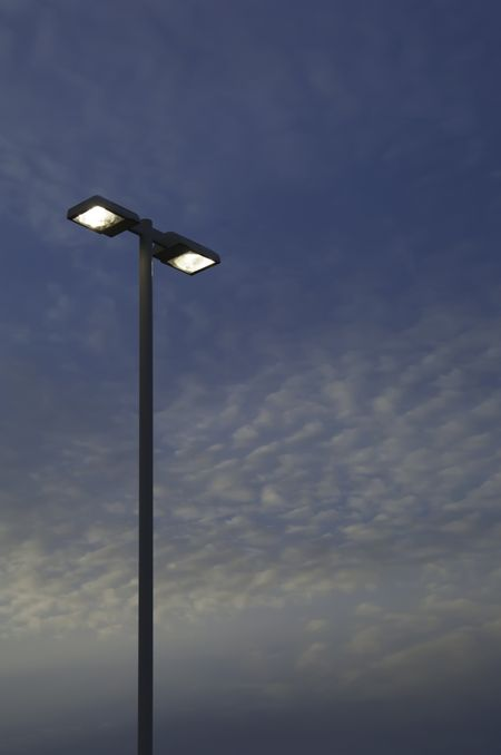 Two high outdoor lights against evening sky