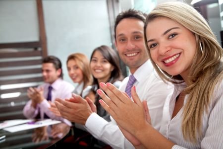 business team clapping in an office facing the camera