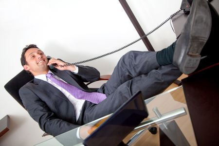 Confident businessman on the phone with his feet on the table