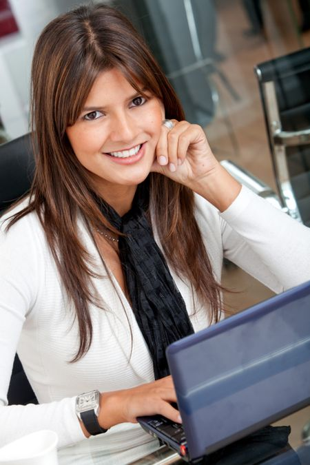 business woman on a laptop in an office smiling