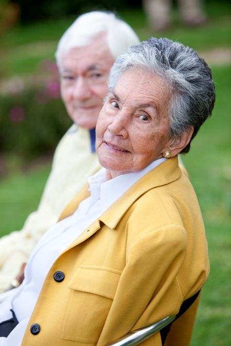 Beautiful elder couple sitting on a bench outdoors