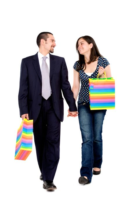 couple walking with shopping bags while talking - isolated over a white background