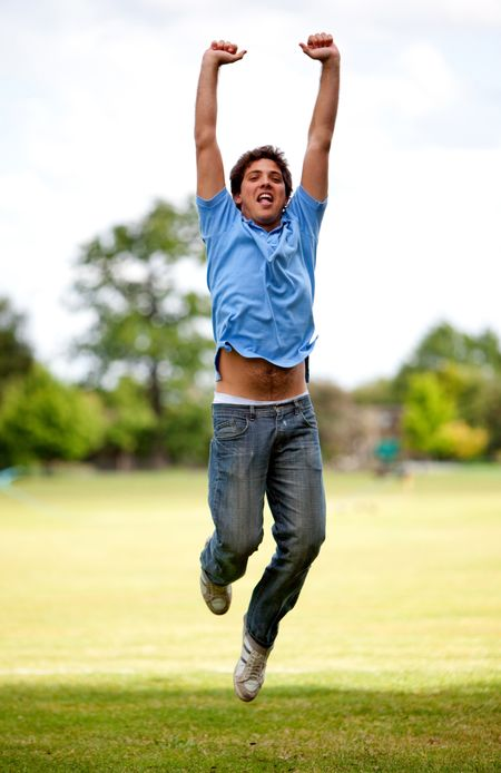Casual young man jumping outdoors from excitement