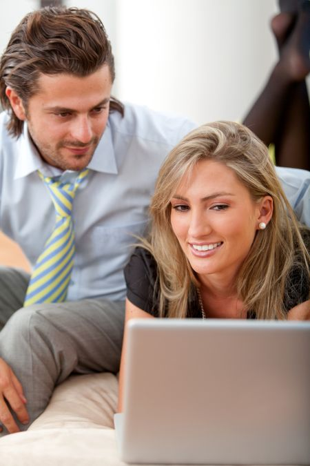 Business couple working with a laptop smiling