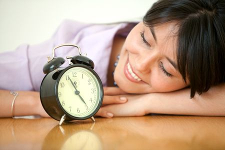 business young woman watching an alarm clock