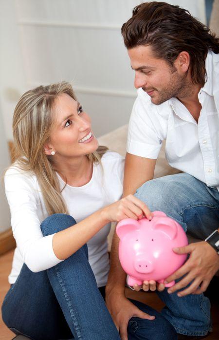 Loving casual couple saving in a piggybank