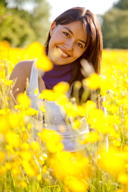 casual woman smiling outdoors with yellow flowers