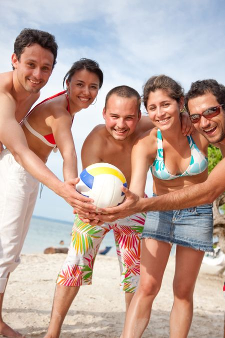 Group of friends standing at the beach with a ball