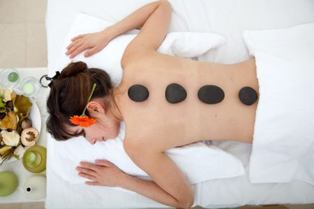 Beautiful woman relaxing at a spa with stones on her back
