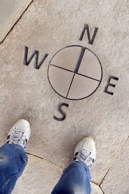 Two feet standing by directional map in stone, north south east west
