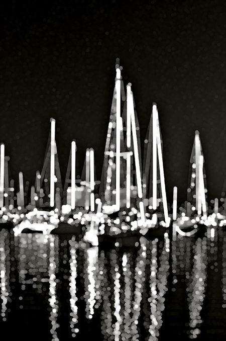 Black and white nocturnal abstract of sailboats with glowing masts and reflections together in a tropical marina (one of a series)