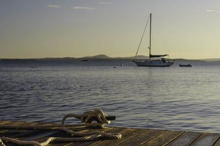 Coastal study in nautical preference: Rope tied to cleat on dock in foreground to secure a boat off camera, while a sailboat lies at anchor beyond, at sunrise in New England (foreground focus)