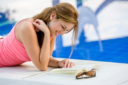 Beautiful woman reading a book by the swimming pool