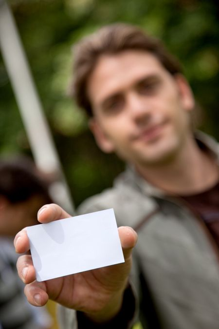 Handsome man displaying his personal card outdoors