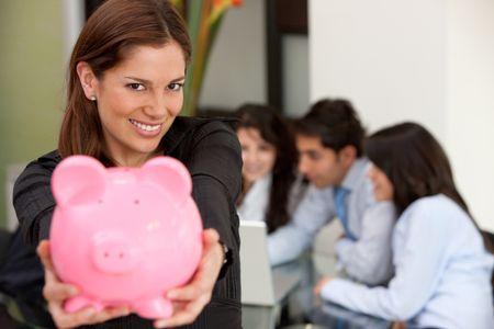 Business woman at an office holding a piggy bank