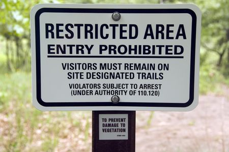 Warning sign by trail in state park: RESTRICTED AREA . . . VIOLATORS SUBJECT TO ARREST . . .