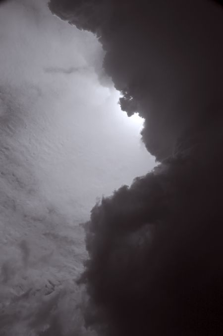 Storm cloud blocking sun high in the sky, mid day, black and white
