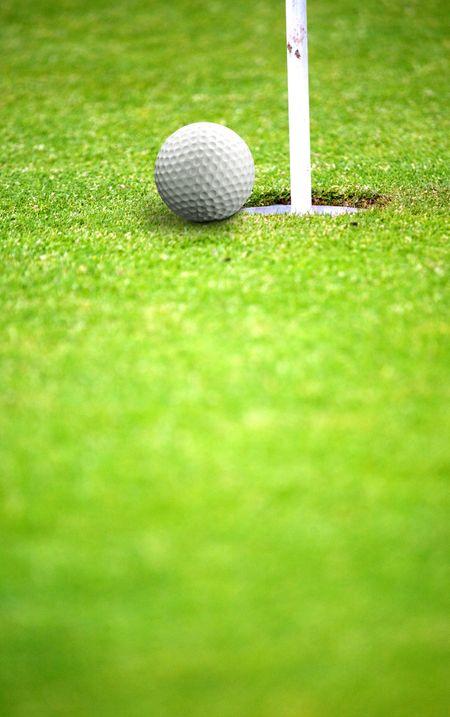 golf ball very near a flag hole