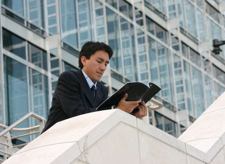 business man reading a magazine in a corporate environment