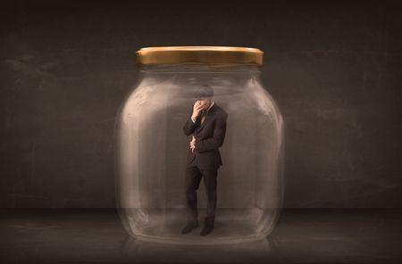 Businessman shut into a glass jar concept on background