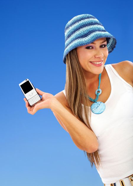Beautiful woman holding a cel phone isolated over blue