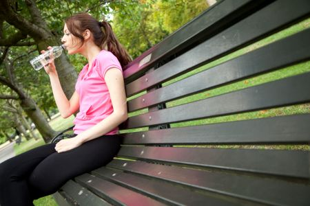 Woman sitting on a bench outdoors drinking water