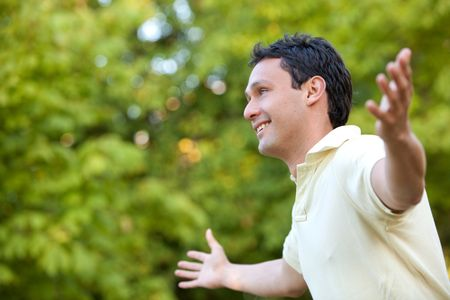 Man smiling outdoors with his arms opened