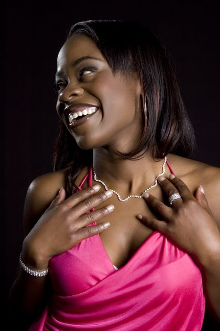Pretty young African-American woman in pink dress looks to her right, smiling, with bare shoulders, jewelry, hands above her breasts