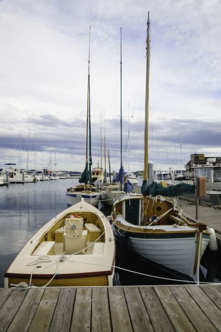 Painterly realistic view of boats tied up in a coastal marina on an overcast day in the Pacific Northwest, for themes of lifestyle or travel