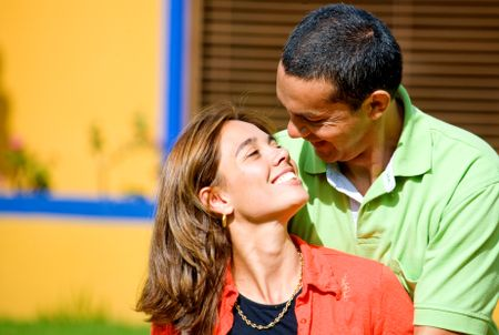couple having fun and smiling at each other outdoors in their home
