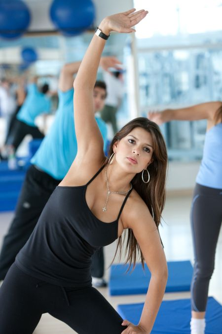Group of people doing stretching exercises at the gym