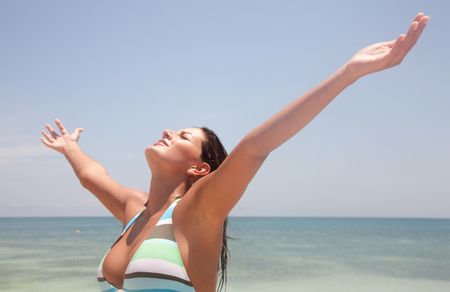 Relaxed woman with arms outstretched at the beach