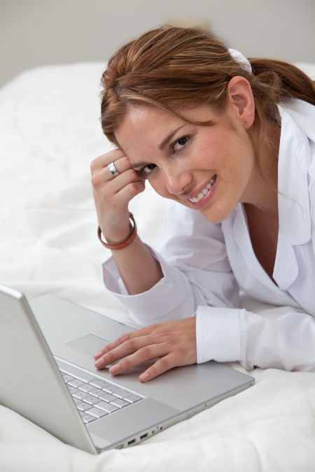Woman in bed working on a laptop computer