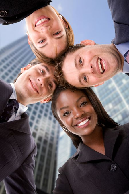 Business team with heads together with corporate buildings behind