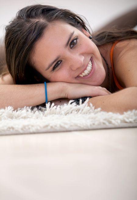Smiley girl lying on the floor over a rug