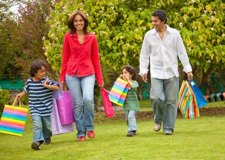 Beautiful happy family with shopping bags outdoors
