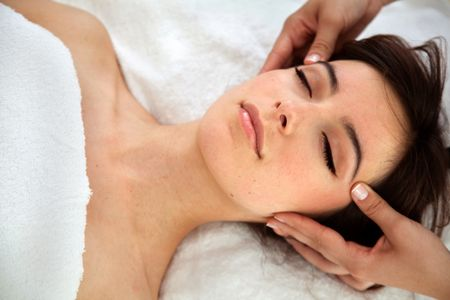 Beautiful relaxed woman getting a facial treatment