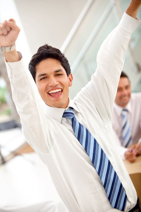 Excited business man with arms outstretched in an office