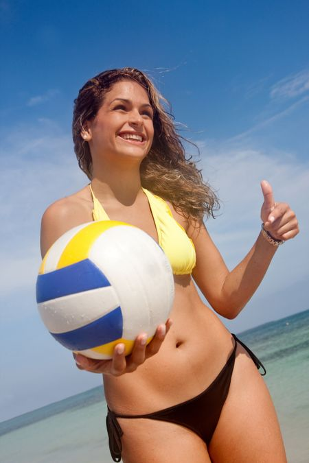Bikini woman at the beach with a volleyball