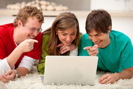 Happy group of friends with a laptop pointing at the screen