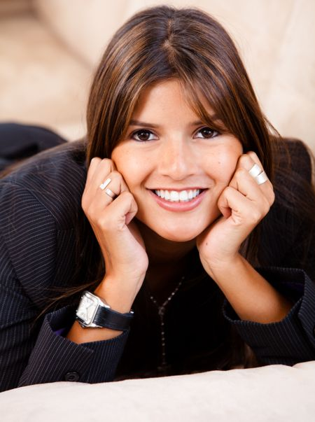 Business woman smiling lying on a couch