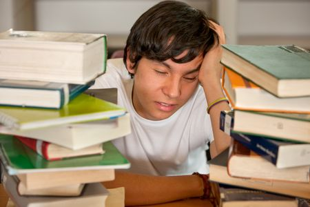 Tired student at the library with books